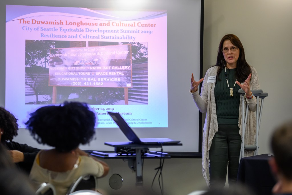 """Photo description: Woman speaking in front of a projected image from a slide show that says """"The Duwamish Longhouse and Cultural Center. City of Seattle Equitable Development Summit 2019: Resilience and Cultural Sustainability."""""""
