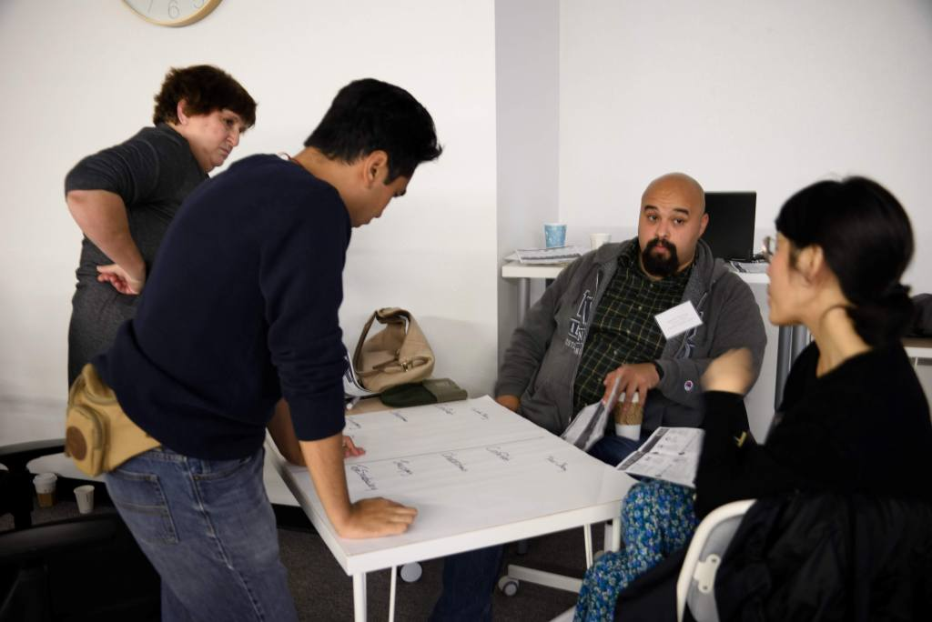Photo Description: Multiracial group of 4 sit and stand in discussion around a table with a large paper with writing on it.