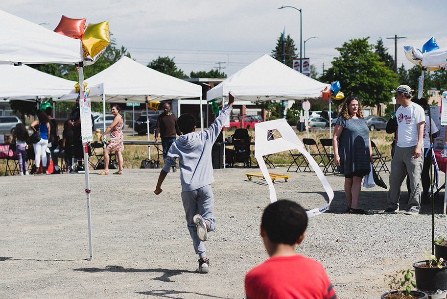 A child wearing a grey outfit runs holding and lifting up a white kite behind him amidst a series of white awnings set up in an outdoor area where others are congregating.